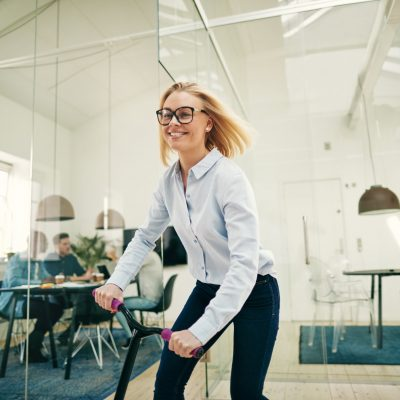 smiling-young-businesswoman-riding-a-scooter-in-an-office.jpg
